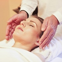 Reiki treatment with hands at the temples