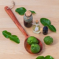 Essential oil bottles with green fruit and leaves