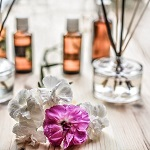 White and purple flowers with aromatherapy diffuser and oils in the background
