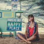 Girl sitting cross-legged next to a sign reading my happy place