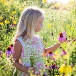 Young girl in a field surrounded by flowers