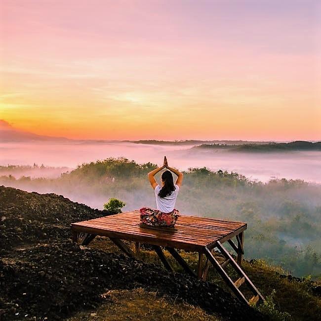 Lady meditating on a platform overlooking a misty landscape
