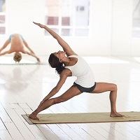Hatha Yoga stretching pose in foreground and background