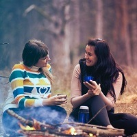 Two friends chat around a camp fire