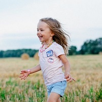 A smiling child runs through a field