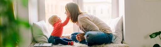 Happy mother and child facing each other on a sunlit window seat