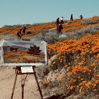 Artist's easel and painting of landscape with people and orange flowers