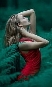 Woman wearing a red dress in the forest