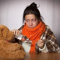 A woman is wrapped up warmly, appearing to have the flu, pouring medicine next to her teddy bear