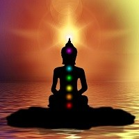 Silhouette of person meditating with chakra points lit in their representative colours