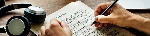 Headphones and person writing sheet music