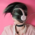 Head and shoulder shot of a girl wearing pink headphones