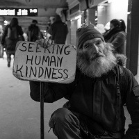 Homeless man holding a sign saying seeking human kindness