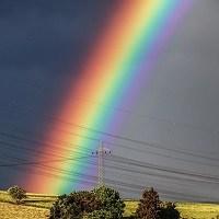A rainbow stretches across a dark grey sky