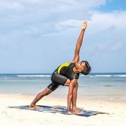 Man holding yoga pose on the beach