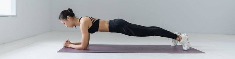 Profile of woman holding the plank yoga pose