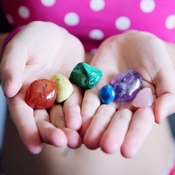 A girl holds her palms open to display a collection on vividly-coloured gemstones